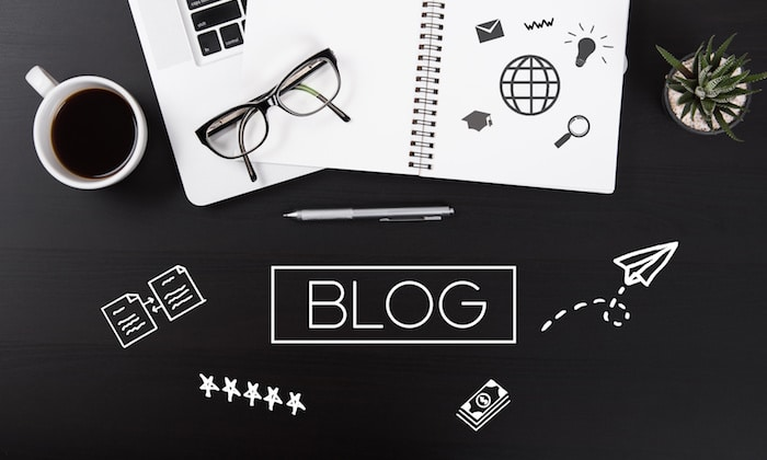 Fundo preto, uma caneca de café, papel e caneta. É tudo que você precisa para começar a escrever no seu Blog e educar os clientes imobiliários online.