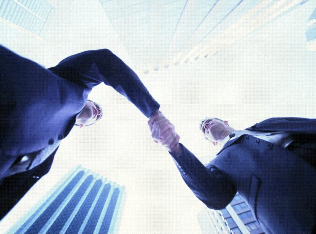 Dois homens visto de baixo para cima, apertando as mãos em um centro comercial. Oferta ativa de imóveis fecham mais negócio