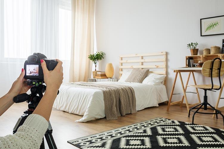 Corretora de imóveis fotografando o dormitório. A corretora está posicionando a câmera para enquadrar a cama de casal, a janela, o criado mudo a esquerda da cama e a escrivaninha a direita.
