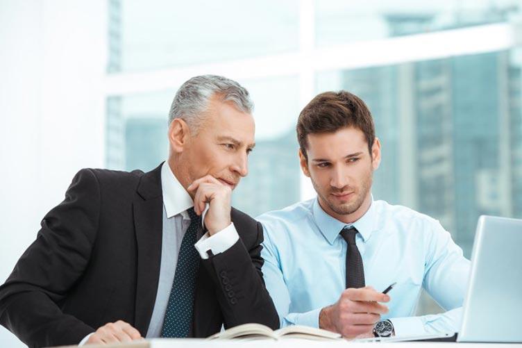 Consultor de imóveis atendendo ao cliente e apresentando imóveis no computador antes da visita.