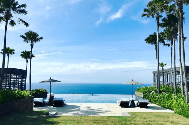 foto linda de um imóvel de reserva para aluguel de temporada. Com piscina de borda infinita e de frente para o mar. Um gramado próximo até a piscina e árvores em volta.