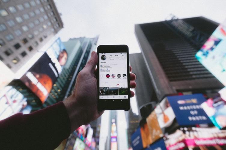 Uma mão, na rua, segurando o celular que está com o aplicativo do Instagram aberto. Primeira forma de anúncios para corretores de imóveis