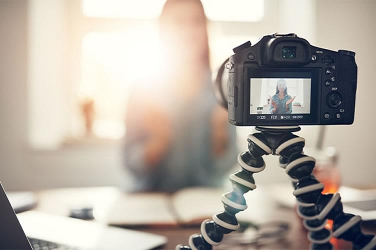 No primeiro plano da imagem uma câmera profissional, ao fundo e embraçado uma corretora de imóveis gravando vídeos para anúncios de imóveis