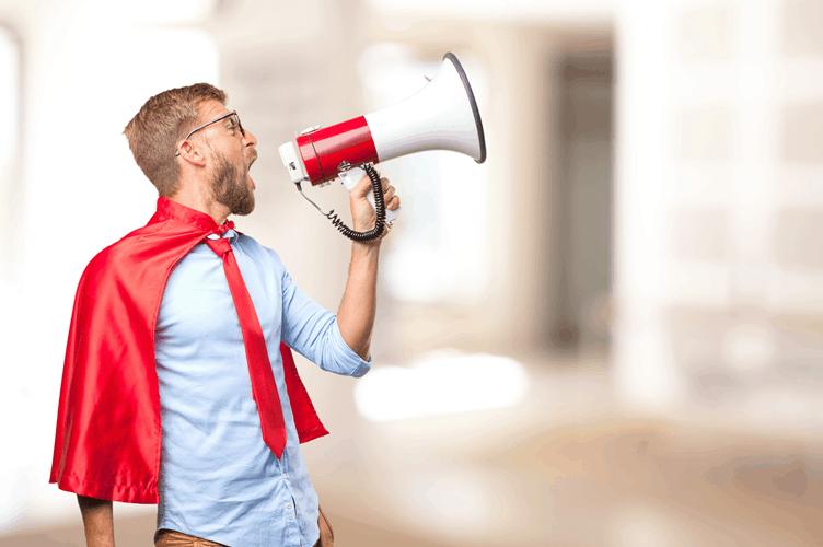 corretor de imóveis vestido de super herói com capa vermelha e um alto falante vermelho e branco para fazer anúncios encantadores para vender um imóvel.