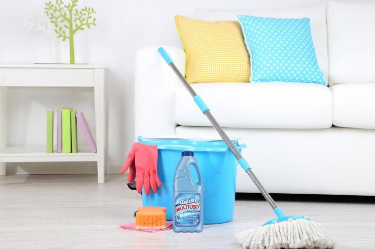 Um lindo sofá branco ao fundo, com almofadas em um tom amarelo e azul bebê. Na frente do sofá um balda com esfregão e produtos de limpeza. Ao lado do sofá um pequeno aparador com livros. A limpeza do imóvel é muito importante na apresentação.