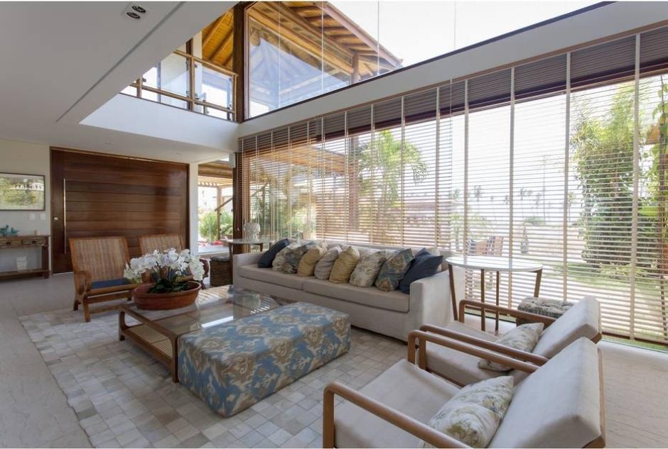 Apresentação do imóvel com luz natural. Uma sala de estar enorme com uma janela tão grande quanto.
