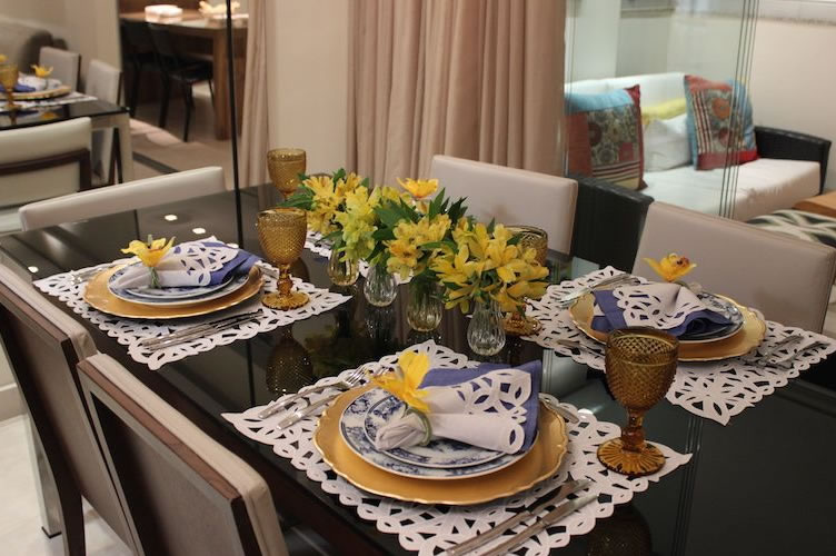 Mesa de jantar posta com arranjo de flores amarelas em cima. Pronta para uma excelente apresentação do imóvel.