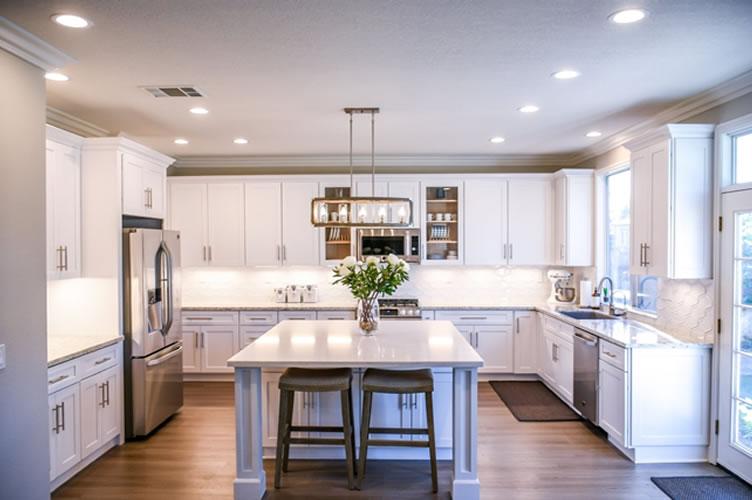 Cozinha toda reformada com armários brancos e paredes em tons neutros. Pronta para apresentação do imóvel.