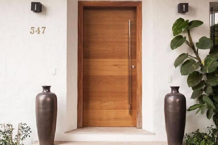 Porta de entrada da casa com plantas para enfeitar.