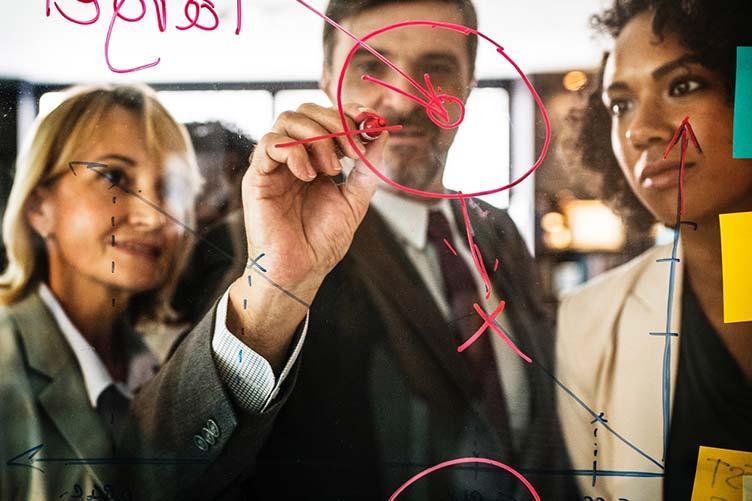 Gerente imobiliário fazendo anotações com marca texto no quadro transparente enquanto é observado por duas corretoras de imóveis