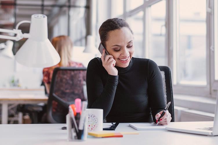 Mulher negra, de cabelo preso e um lindo sorriso no rosto trabalhando como assistente imobiliário. Ao telefone em uma ligação e fazendo anotações. Ao lado tem uma caneca e na frente um notebook branco.