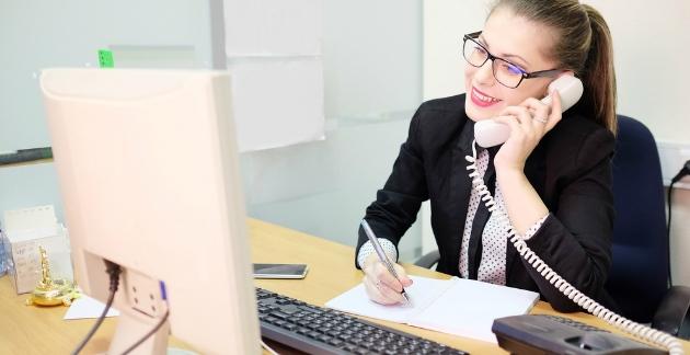 Uma mulher loira, de cabelos presos e óculos trabalhando feliz como assistente Imobiliário