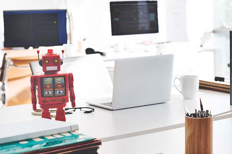 Um robô ao lado de um notebook branco na imobiliária. Para simbolizar a utilização de chatbot para automatizar o marketing imobiliário.
