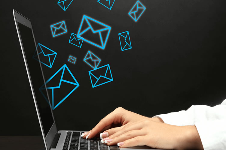 As mãos da corretora de imóveis no notebook com diversos envelopes flutuantes. Simbolizando a automação de e-mail marketing