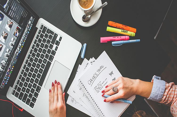 corretora de imóveis com o notebook na frente e um caderno de anotações para criar conteúdo para o blog imobiliário e automatizar o marketing imobiliário.