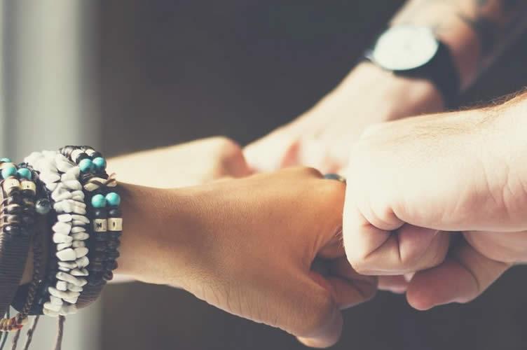 Mãos de punho cerrado se unindo ao centro. Trabalho em equipe e network é uma vantagem de trabalhar no plantão de vendas