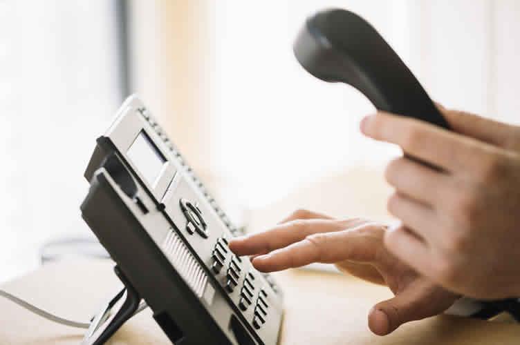 Corretor de imóveis ao telefone para iniciar uma abordagem durante a captação.