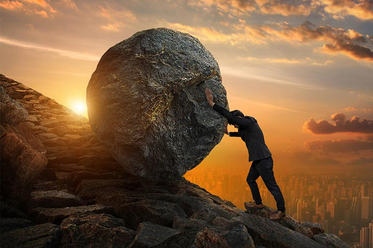 Captador de imóvel empurrando uma grande rocha morro acima com o sol e a cidade ao fundo