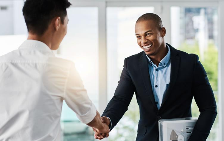Corretor de imóveis feliz e muito sorridente fechando uma exclusividade com um cliente graças ao guia que ele fez para captar imóveis. que está em suas mãos.