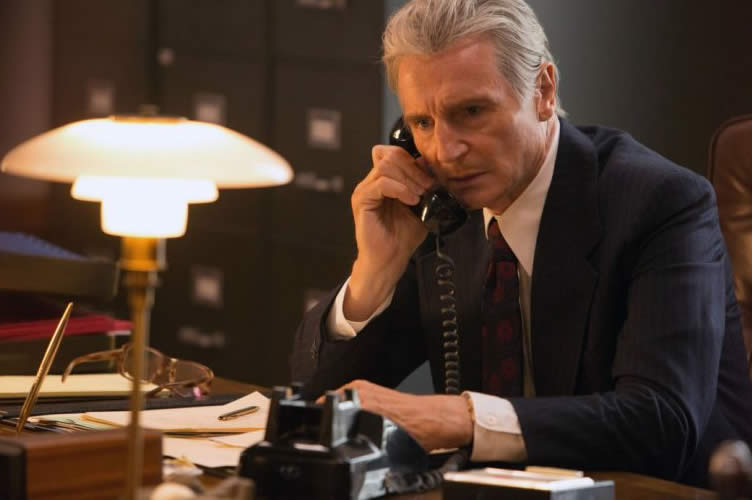 Liam Neeson atendendo ao telefone de terno e gravata. Cold Call no mercado imobiliário