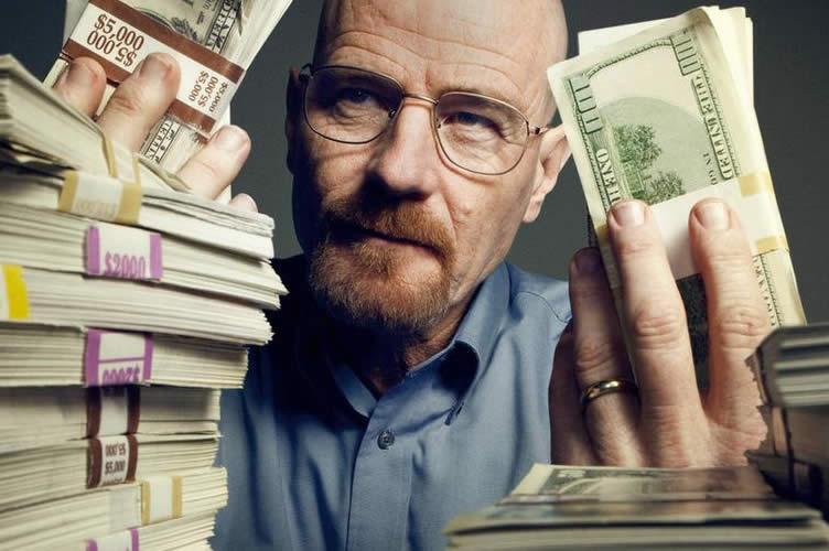 Corretor com uma pilha de dinheiro em uma mesa e segurando alguns dólares. Comissão do corretor de imóveis