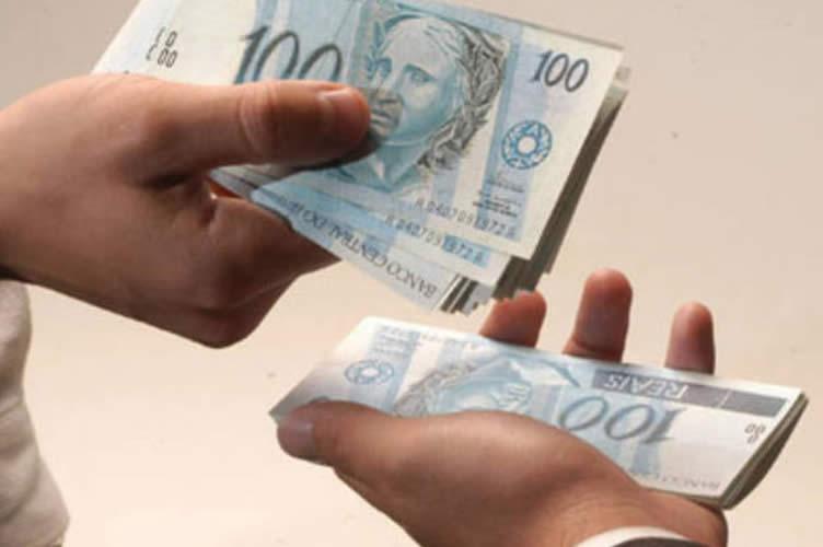 Duas mãos segurando dinheiro igualmente repartido. Da comissão do corretor de imóveis