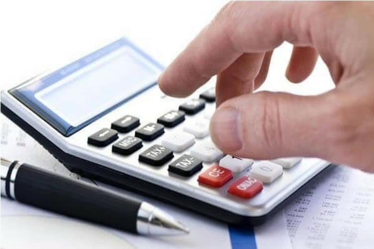 uma mão bem acentuada mexendo em uma calculadora, com uma caneta preta ao lado e folhas de papel embaixo.