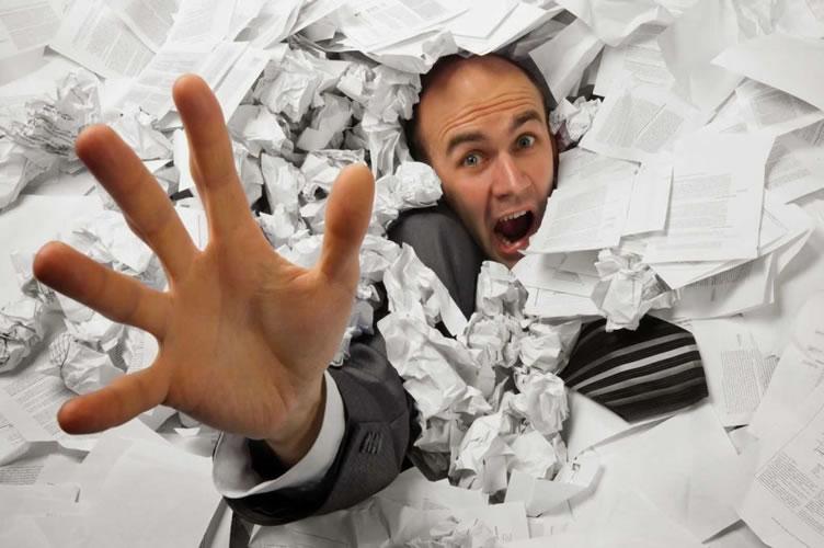 Homem de terno, afogado em papeis e documentos desorganizados. Com a mão estendida pede por ajuda para gerenciar sua imobiliária.