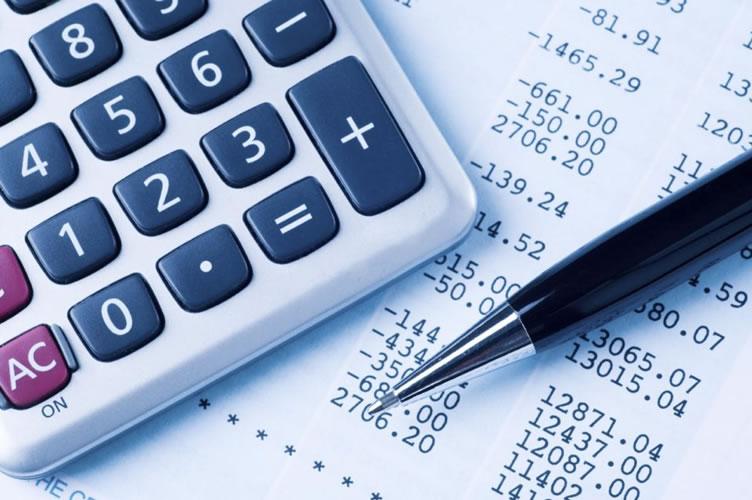 Uma calculadora, nota fiscal ao fundo e uma caneta. A gestão financeira é fundamental para o gerenciamento de uma imobiliária.