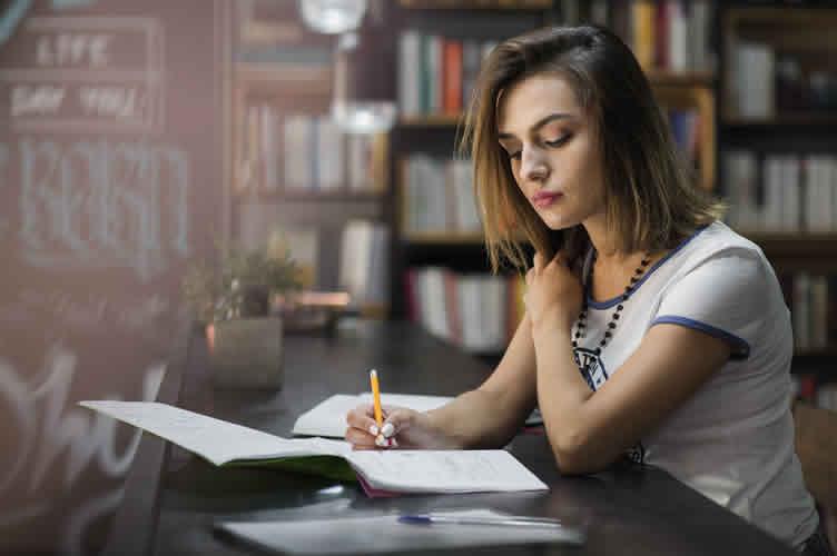 Corretora de imóveis sentada em uma livraria para estudar.