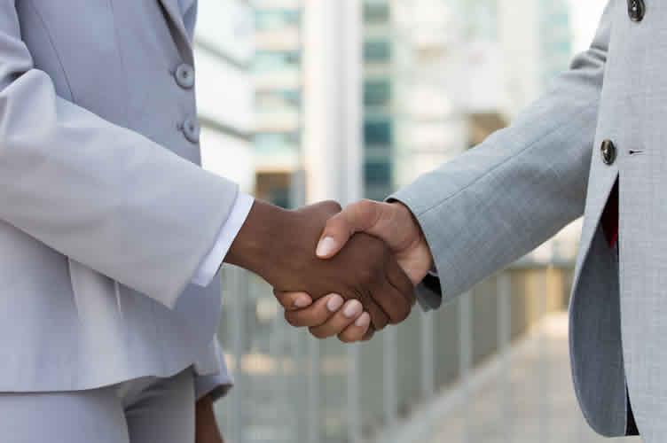 Corretor e Proprietário fechando o contrato de captação de imóveis com um aprto de mãos.