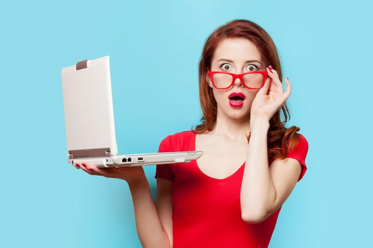 Mulher linda de vestido vermelho e óculos vermelho com um notebook na mão e boca aberta de espanto. Lendo um artigo escrito por um corretor de imóveis para captar clientes.