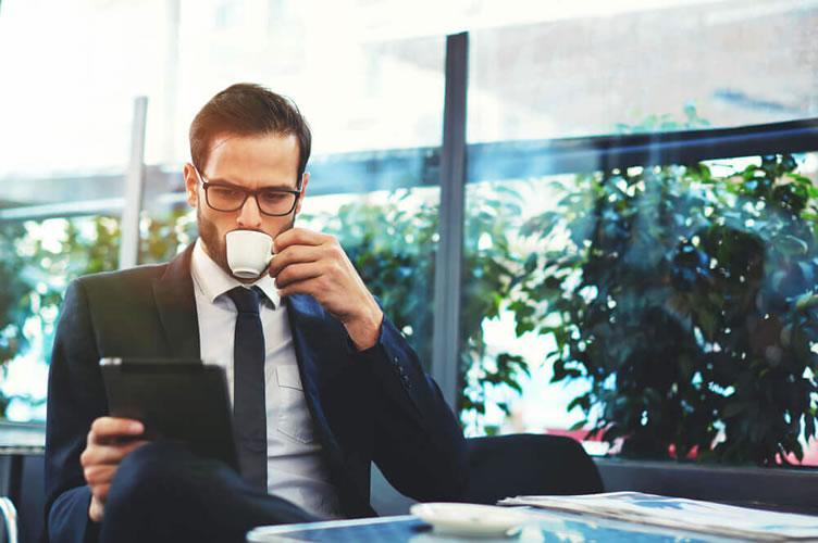 Corretor de imóveis de terno tomando um café, com óculos e um tablet nas mãos observando suas redes sociais.