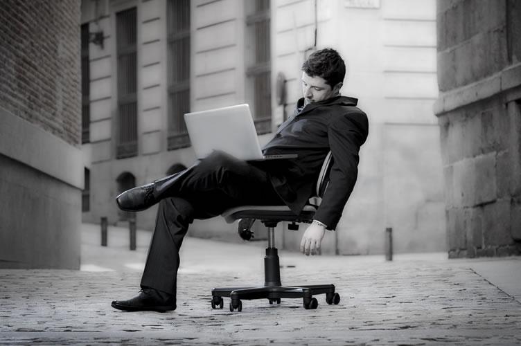 Corretor de imóveis com terno e notebook no colo. Ele está sentado em uma cadeira no meio do nada e exausto por não conseguir clientes para o seu negócio.