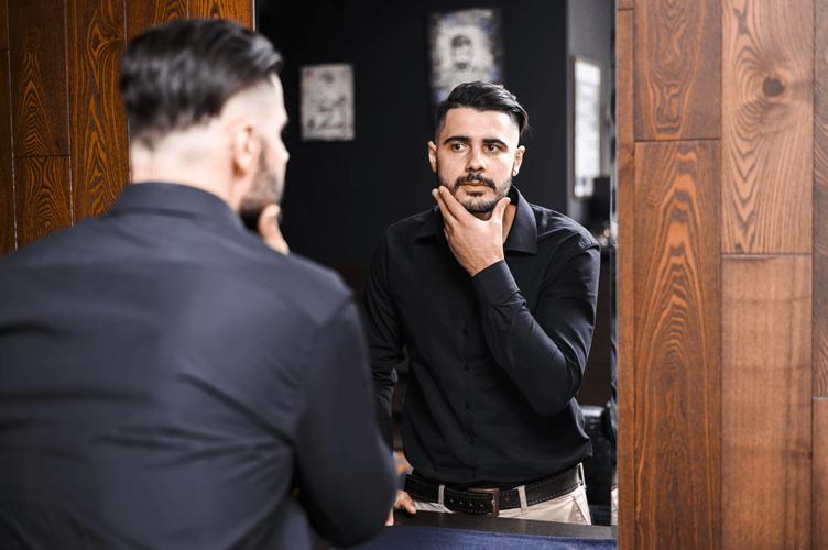 corretor de imóveis com camisa social preta se olhando no espelho com a mão no rosto.