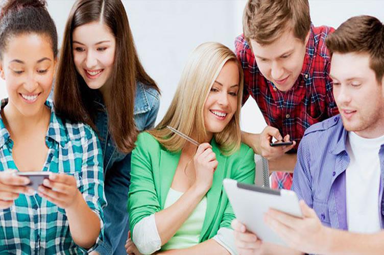 5 corretores da geração Z trabalhando em parceria fazendo uso da tecnologia. 3 mulheres, sendo duas morenas e 2 homens loiros. Todos sorrindo e descontraídos.