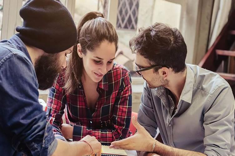 3 corretores da geração Z observando uma agenda de compromissos e debatendo sobre horário de trabalho. Onde preferem mais flexibilidade.