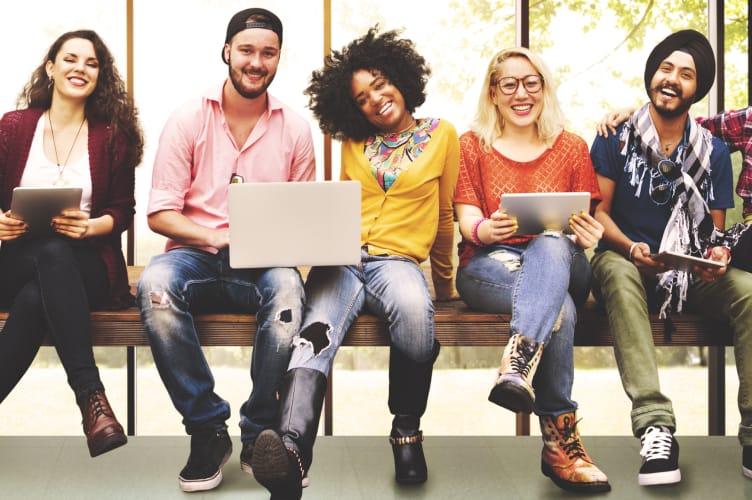 6 corretores da geração Z com seus celulares, tablets e notebooks sorrindo despretensiosamente.