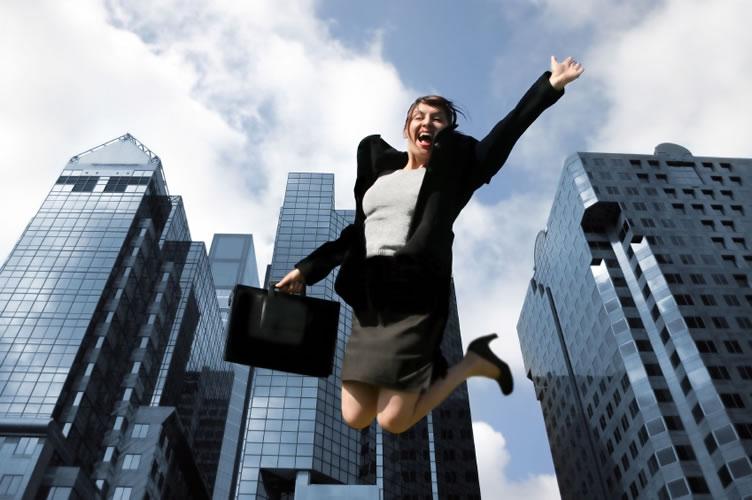Corretora de imóveis saltando alto com sua pasta na mão e muito feliz por ter alcançado o sucesso.