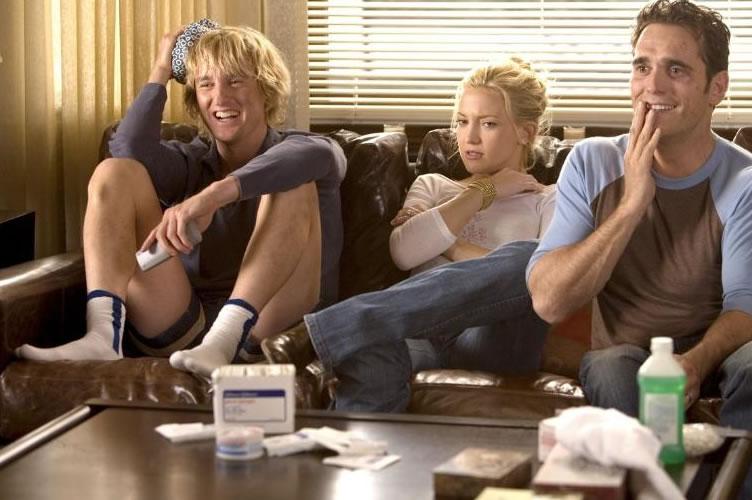 Cena do filme dois é bom e três é demais, onde os atores estão sentados no sofá com cara de surpresos. Perfeito para a promoção especial nas descrições de anúncios de imóveis