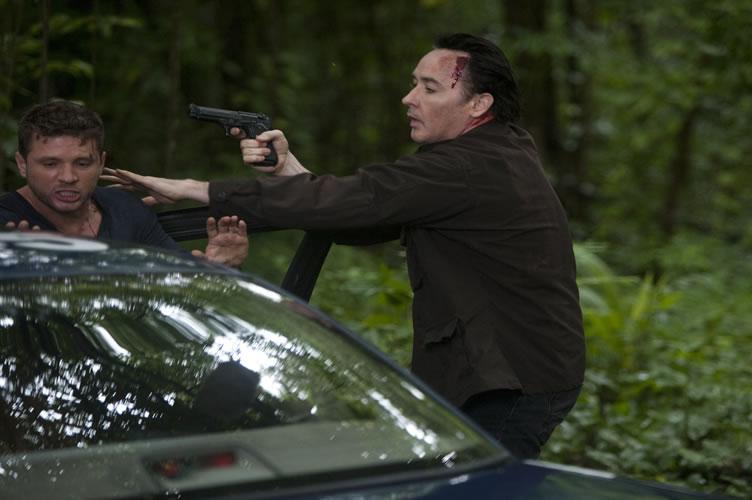 Cena de filme de ação, onde o ator aponta uma arma para o outro para ele executar algo. Apela a ação
