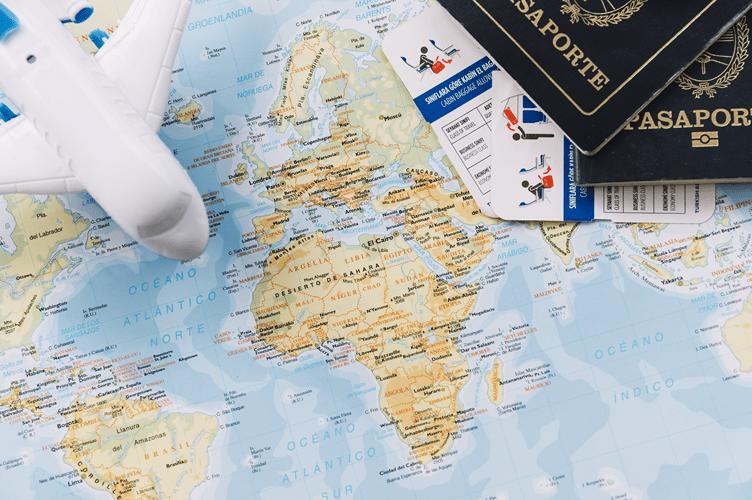 foto de dois passaportes, passagens aéreas em cima do mapa múndi. Os documentos necessários para vender imóveis no Brasil para estrangeiros.