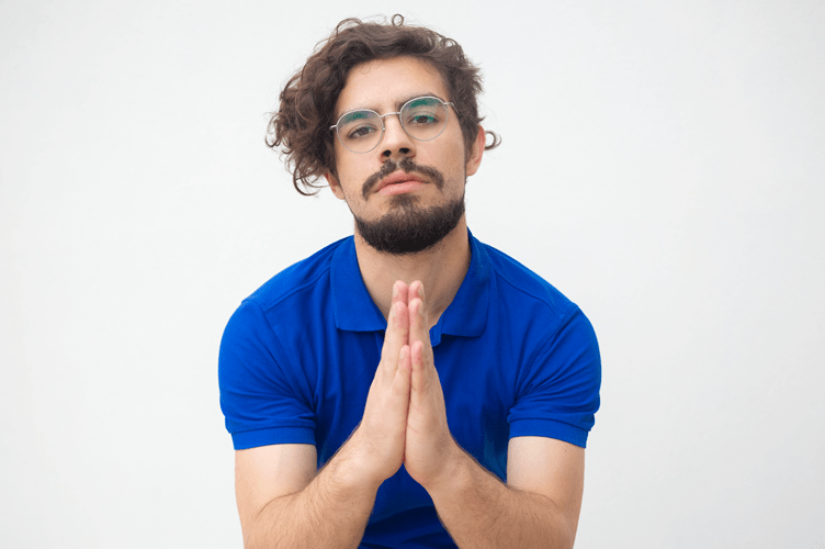 Corretor de imóveis com as mãos juntas como se estivesse rezando para seu lead abrir o e-mail marketing