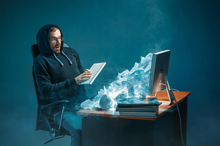 Corretor de imóveis com um teclado na mão e vários papeis amassados na mesa. Com a boca aberta para escrever o melhor e-mail marketing do mercado imobiliário