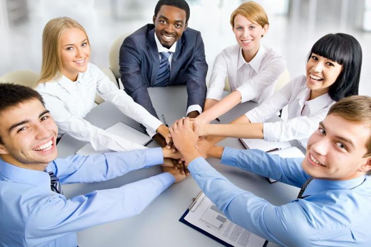 6 corretores de imóveis, integrantes de uma equipe imobiliária, de mãos dadas sentados em uma mesa. Super motivados para trabalhar.