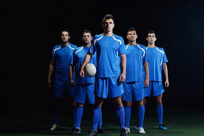 5 integrantes de um time de futebol. Com um lider a frente segurando a bola em seus braços. A seleção de uma equipe imobiliária deve seguir esse padrão de qualidade.
