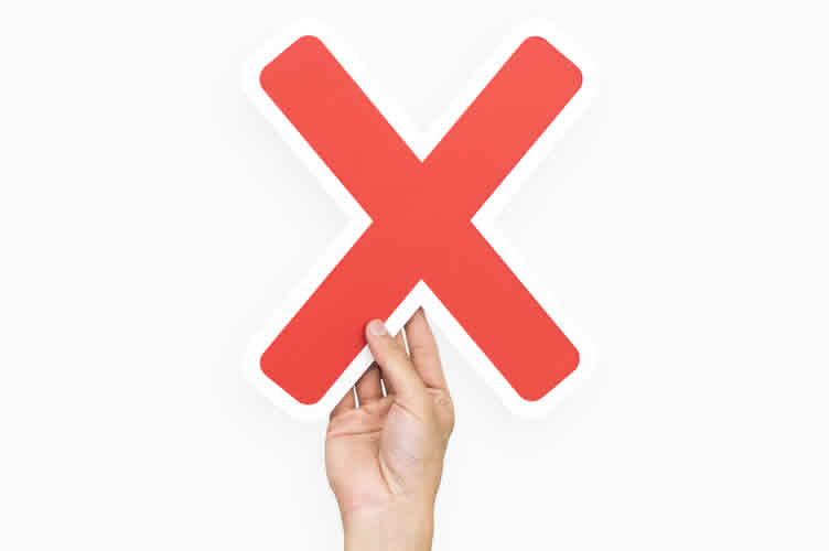 Mão segurando um X vermelho para indicar os maiores erros ao ofertar imóveis por telefone.