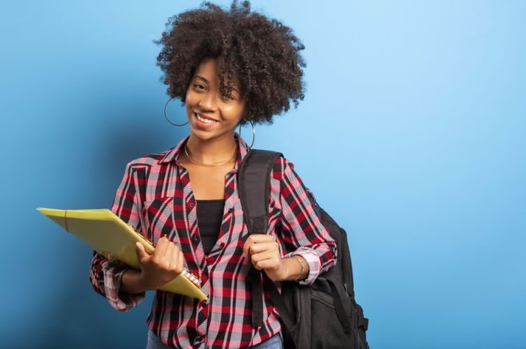 Moça negra com cabelo afro, muito feliz por ter concluído o curso de negócios imobiliários.