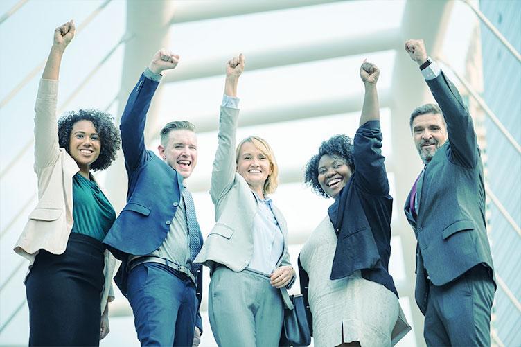 5 corretores entre homens e mulheres lado a lado com o punho levantado em sinal de vitória e união.