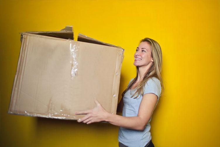 Mulher carregando caixa da mudança após a compra do imóvel transparente e segura.